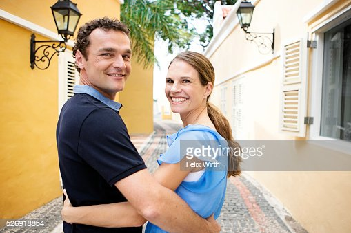 Man embracing woman on narrow street : Stock Photo
