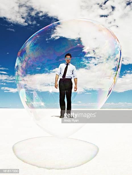 Man enclosed in giant bubble on salt flats.