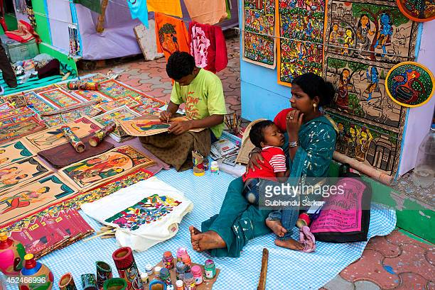 A man engaged in making handicraft products while his wife takes care of their sleeping child Handicraft products of West Bengal are world famous...