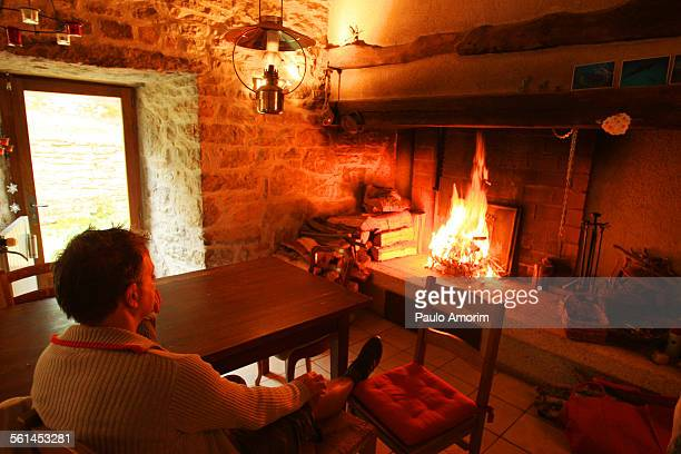 A man enjoy in front of the fireplace at home