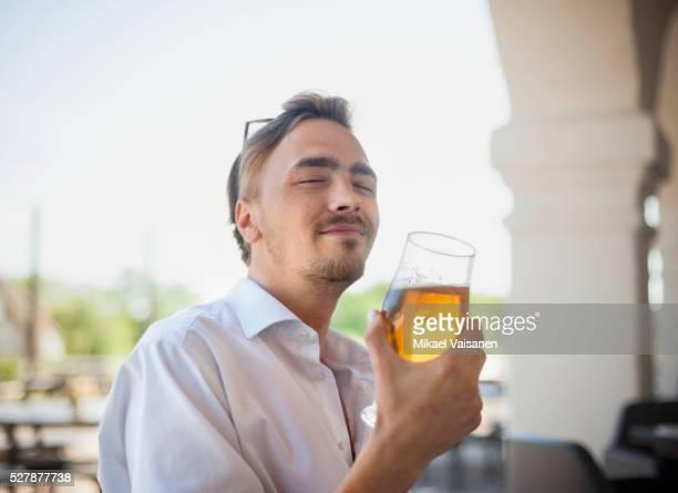 man enjoying a beer in an outdoor restaurant