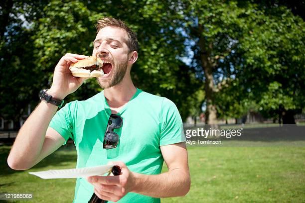 A Man Enjoying a Burger in a City Park