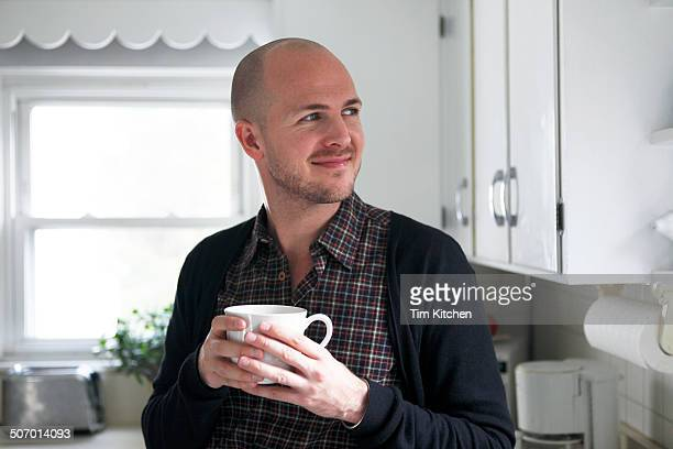 Man enjoying a cup of coffee in kitchen