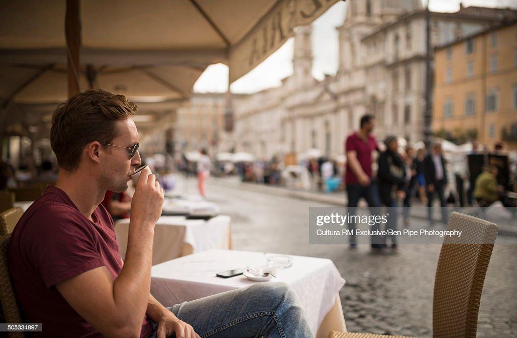 Man enjoying espresso at restaurant, Piazza Navona, Rome, Italy