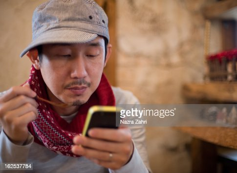 Man enjoying lunch while looking at smartphone : Stock Photo