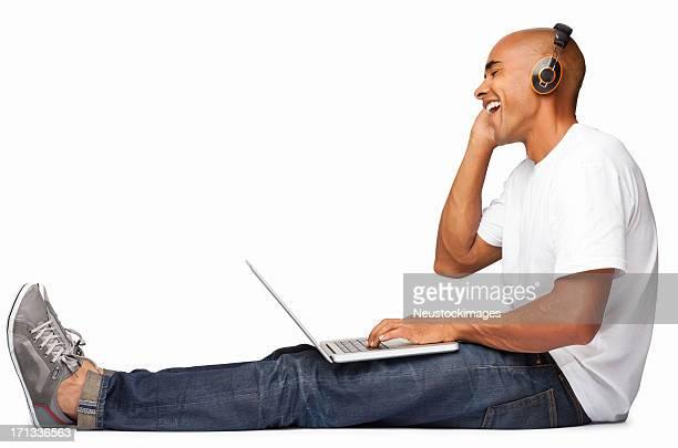 Man Enjoying Music While Using Laptop - Isolated