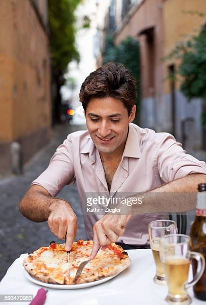 man enjoying pizza and beer at a restaurant