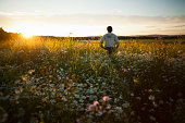 Man enjoying sunset on field, Sarsy village, Sverdlovsk region, Russia