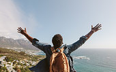 Rear view of young guy with backpack standing outdoors with arms spread open against seascape. Man enjoying the view from the top of the mountain.