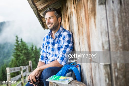 Man enjoying the view from wooden shack, Tirol, Austria