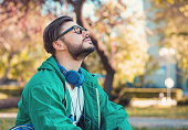 Hipster man in headphones and glasses keeping eyes closed and enjoying fresh air in summer park