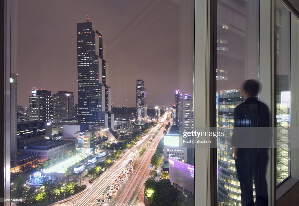 Man enjoying view from window in Seoul : Stock Photo