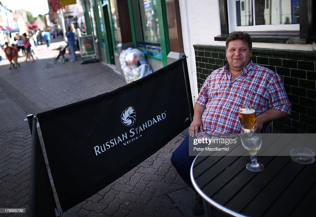 A man enjoys a drink on the High Street on September 2, 2013 in Dartford, England. High Street campaigner Mary Portas is today facing questions from Members of Parliament on the communities and local government select committee. The traditional high street is under increasing pressure due to the recession and the rise of on-line shopping.