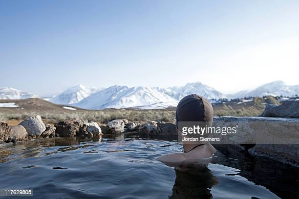 A man enjoys a hot spring near the mountains.