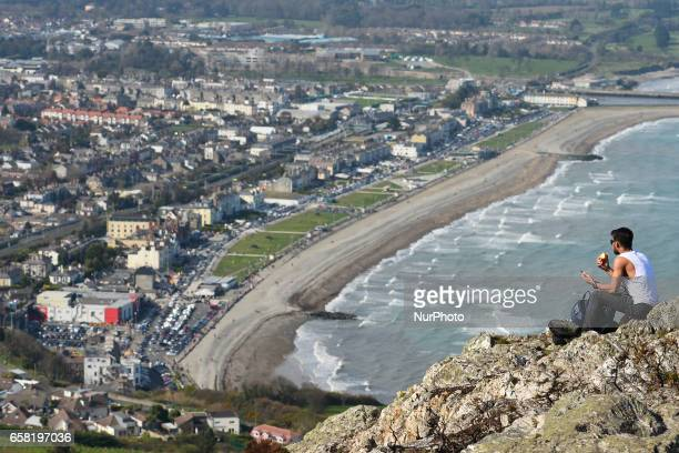 A man enjoys a sunny day sitting on top of Bray Head On Sunday March 26 in Bray Ireland