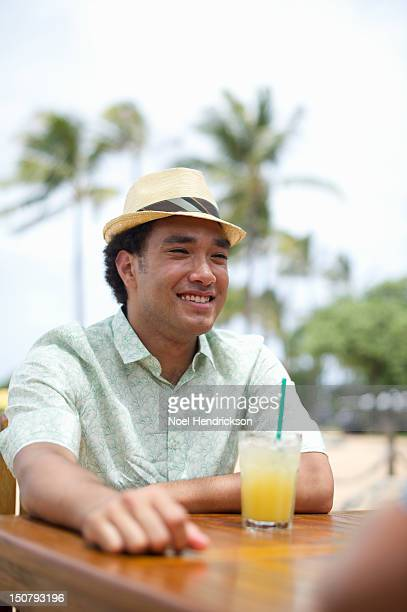 A man enjoys a tropical cocktail at a bar