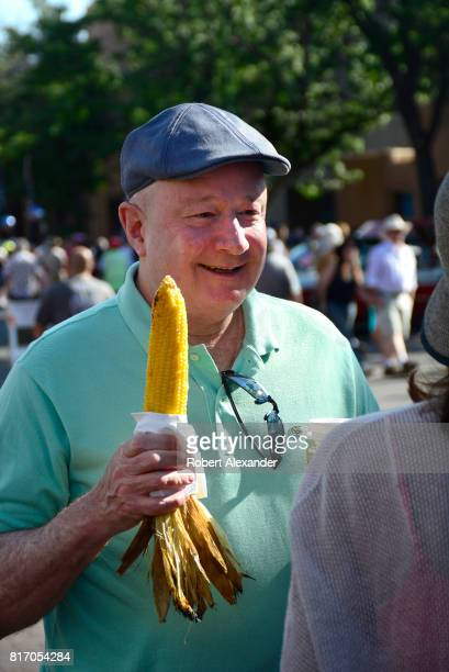 A man enjoys an ear of roasted cornonthecob at a Fourth of July celebration in Santa Fe New Mexico