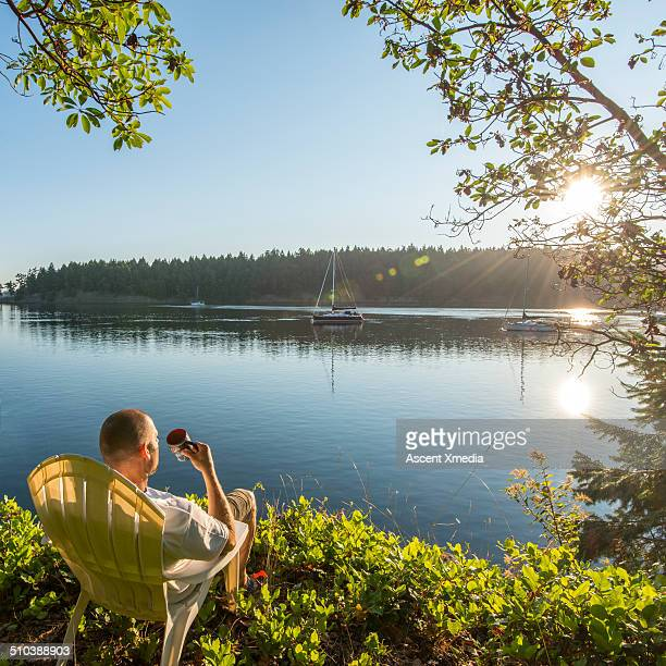 Man enjoys hot beverage while looking across bay