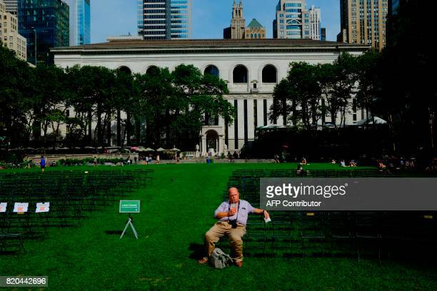 A man enjoys the day at Bryan Park during a sunny day as hot temperatures continue in New York on July 21 2017 / AFP PHOTO / EDUARDO MUNOZ ALVAREZ