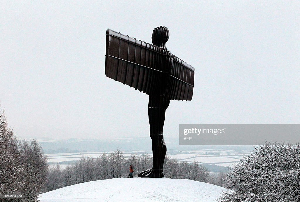 A man enjoys the fresh snow as he walks near The Angel of the North sculpture, over-looking Gateshead, Tyne and Wear in northeast England on January 15, 2013.