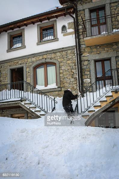A man enter in his house in Campotosto Italy on January 19 2017 A great deal of snow has fallen in the area which was hit by four quakes on Wednesday...