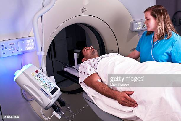 Man entering CAT scan overseen by nurse