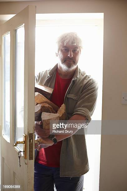Man entering house carrying logs