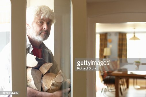 Man entering house carrying logs : Stock Photo