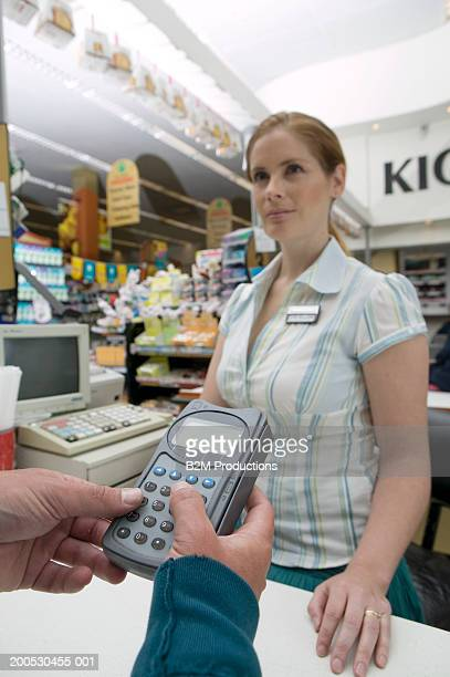 Man entering pin number at checkout, woman looking on