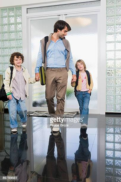 Man entering the house with his children
