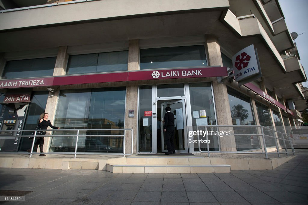 A man enters a branch of Cyprus Popular Bank Pcl, also known as Laiki Bank, as banks open for the first time in two weeks in Nicosia, Cyprus, on Thursday, March 28, 2013. The Central Bank of Cyprus's capital controls will include a 300-euro ($383) daily limit on withdrawals and restrictions on transfers to accounts outside the country. Photographer: Simon Dawson/Bloomberg via Getty Images