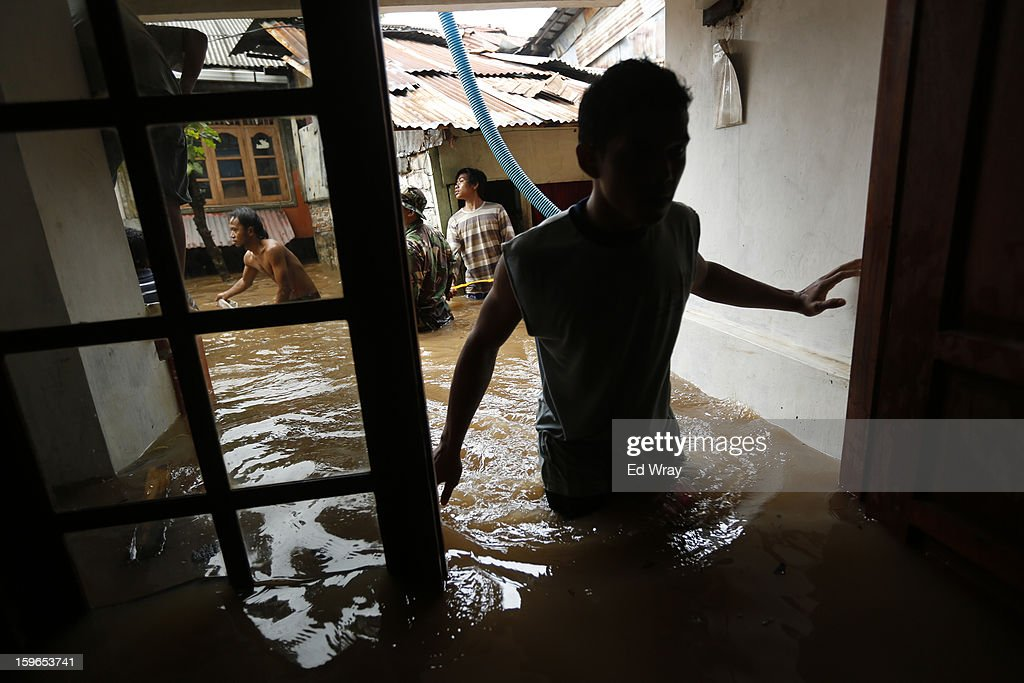 A man enters a flooded home on January 18, 2013 in Jakarta, Indonesia. According to the National Disaster Management Agency, about 50 percent of the capital is under water following the floods which have so far claimed eleven lives and displaced thousands of Indonesians..