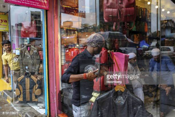 A man enters a leather goods store in the Dharavi area of Mumbai India on Tuesday July 18 2017 India's new goods and services tax introduced on July...