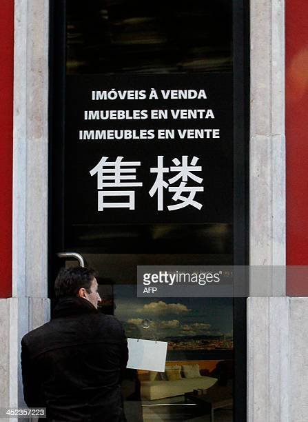 A man enters a real estate office with Chinese characters announcing properties to sell in downtown Lisbon on November 26 2013 A dream home in...