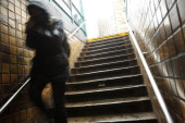 A man enters a subway station in the snow and sleet in the early hours of a major winter storm on February 8 2013 in Brooklyn borough of New York...