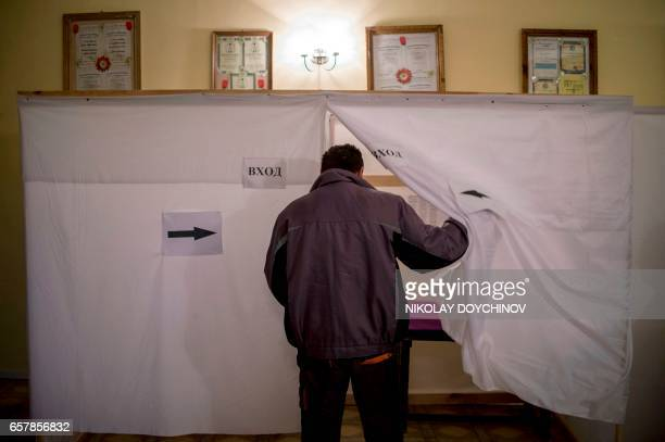A man enters a voting booth before casting his ballot at a polling station in the village of Dolni Bogrov near Sofia on March 26 during the country's...