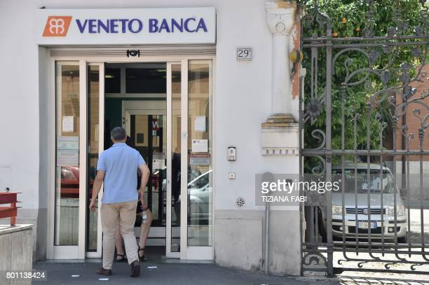 A man enters in a branch of Italian bank 'Veneto Banca' in Rome on June 26 2017 Up to 3900 voluntary redundancies and 600 branch closures are on the...