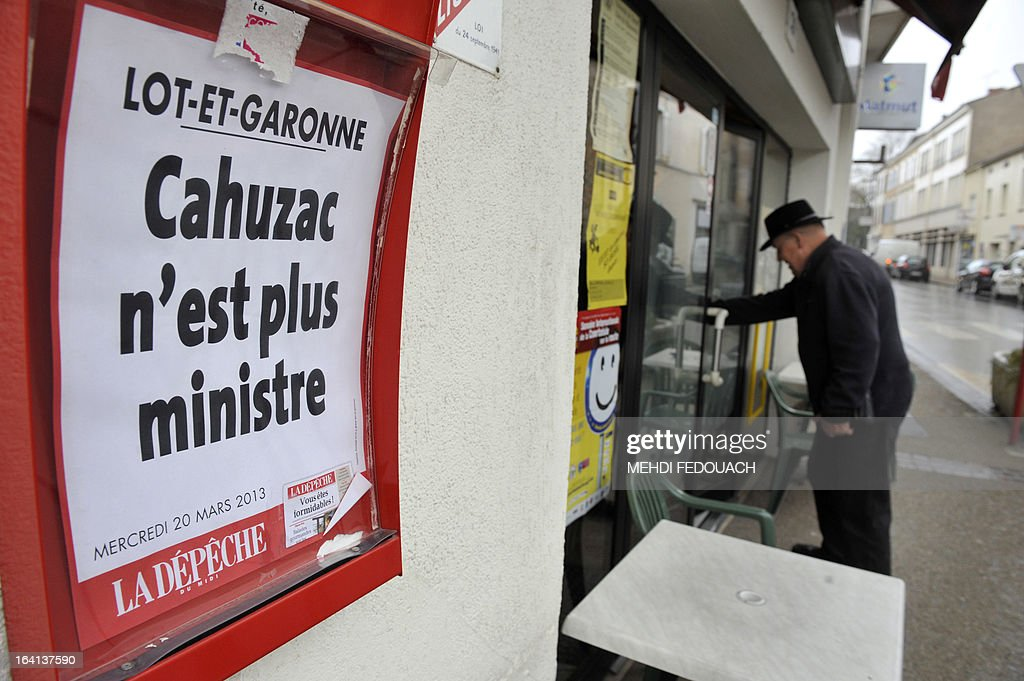 A man enters in a shop near an information board reading the headlines of the regional newspaper La Depeche : 'Cahuzac is no longer Minister', on March 20, 2013 in Villeneuve-sur-Lot, southwestern France. Outgoing French Budget Minister Jerome Cahuzac is the mayor of Villeneuve-sur-Lot city. Cahuzac resigned yesterday after prosecutors announced a probe into a Swiss bank account he allegedly used to hide assets from the tax authorities.