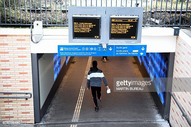 A man enters in a tunnel under two monitor screens alerting of the interuption of the railway trafic due to a catenary pullout on December 7 2016 at...