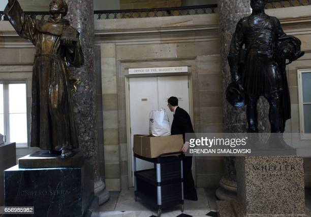 A man enters the majority whip office to bring food to members of the Freedom Caucus that are meeting after coming back from the White House where...