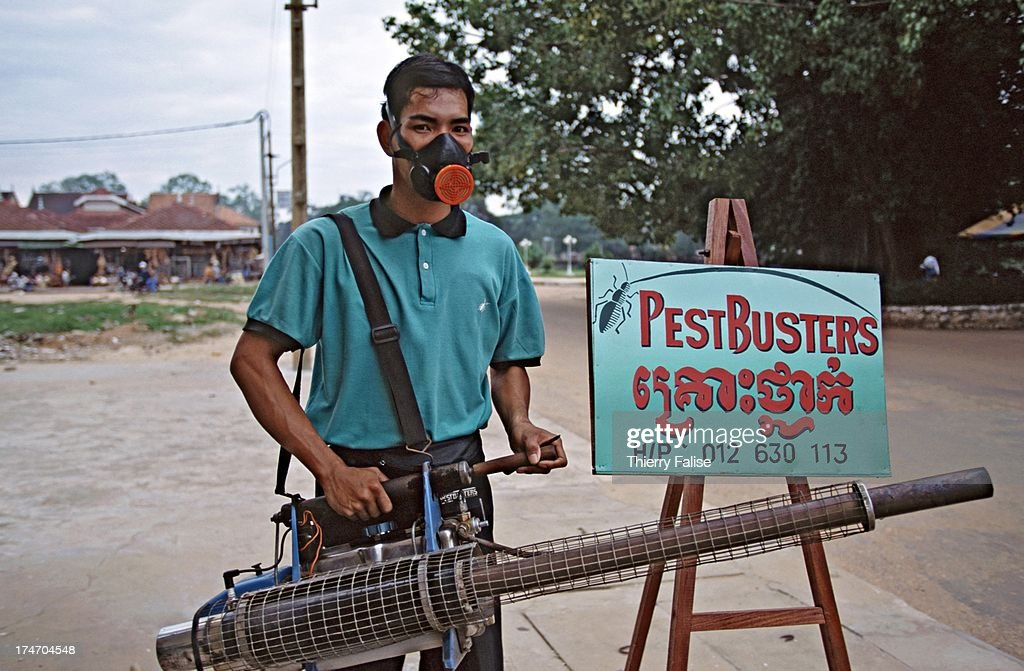 A man equipped with a mask and a airbrush canon is ready to spray chemicals against pest in Siem Reap