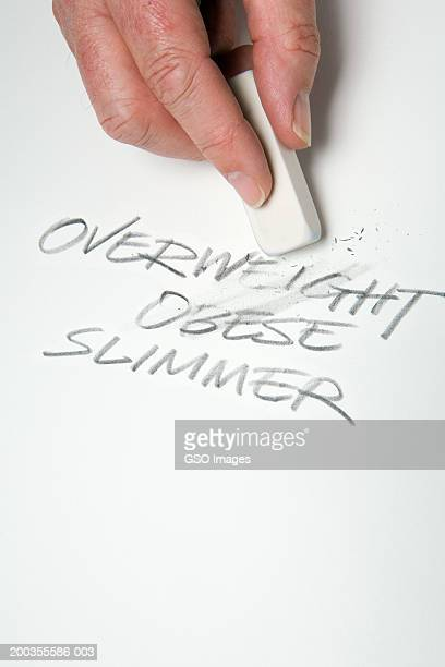 Man erasing words OVERWEIGHT, OBESE and SLIMMER, close-up of hand