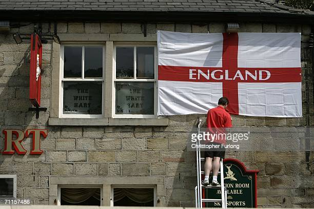 Man erects a St Georges flag on the outside of The White Pub on 6 June Holmfirth England As World Cup fever begins to grip Britain sales of Saint...
