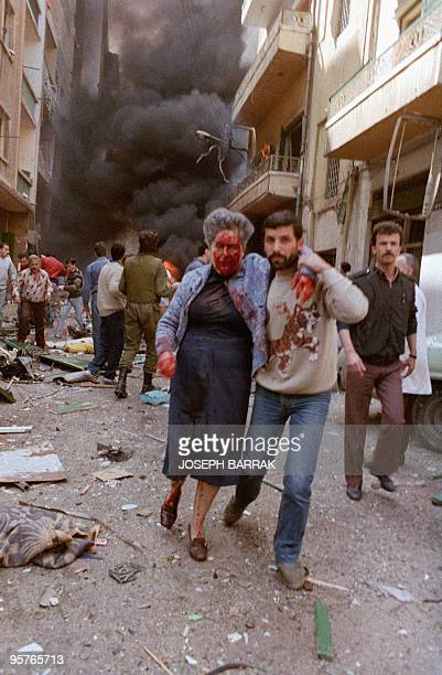 A man evacuates 25 March 1986 an injured woman following a car bomb explosion in the Ashrafieh district of mainly Christian East Beirut The car...