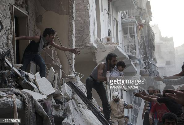 A man evacuates a child from a building following a reported barrel bomb attack by Syrian government forces on the northern Syrian city of Aleppo on...