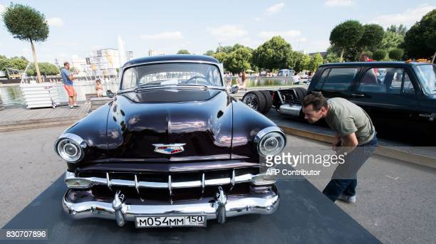 A man examines a classic automobile during the Faces and Laces alternative modern art festival on August 12 2017 in the Gorky Central Park of Culture...