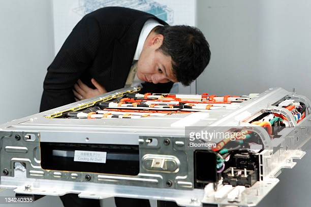 A man examines a lithiumion battery for Toyota Motor Corp's Prius plugin hybrid vehicle during the unveiling in Tokyo Japan on Tuesday Nov 29 2011...