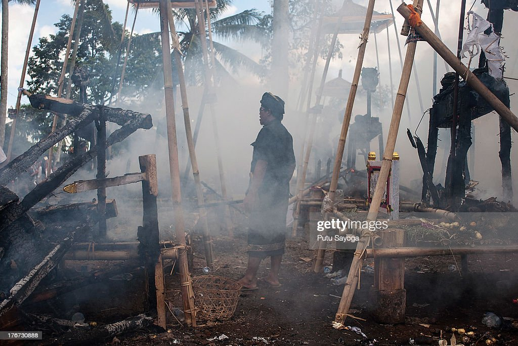 A man examines the burned sarcophagi at the cremaltion site during a Balinese Hindu mass cremation on August 18, 2013 in Ubud, Bali, Indonesia. More than 60 corpses were collectively cremated to share the expense of the ceremony. Well known as Ngaben, it is one of the most important ceremonies for Balinese Hindu people, as they believe it will free the spirit from the deceased body so it can reincarnate.