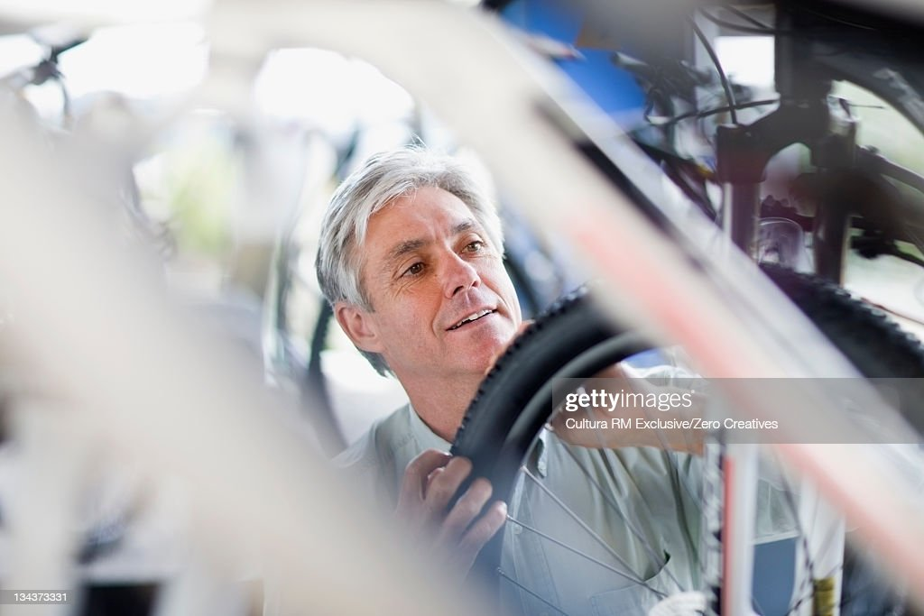 Man examining bicycle tire in shop