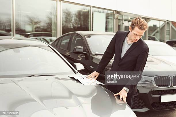 Man examining car outside showroom